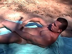 Muscular elated guy jerks off on high a public beach